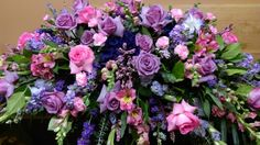 Full casket spray in pinks and purples