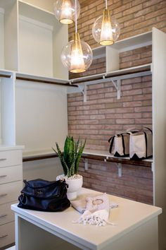 This remodeled contemporary closet features globe pendant lights and built-in shelves and drawers against an exposed brick wall. The shelves and drawers provide plenty of storage space for clothes and accessories.