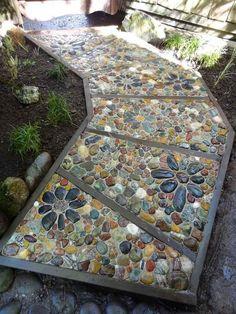 allée de jardin en mosaique de galets à motifs floraux, graminées d'ornement et plantes vertes                                                                                                                                                                                 Plus