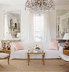 living rooms - white silk drapes silk pink pillows white slip-covered sofa French wood coffee table crystal chandelier silver beveled mirror...