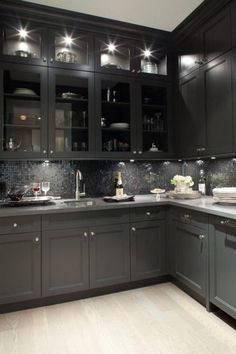 Gorgeous black kitchen design with oak wood floors, black shaker kitchen cabinets, gray quartz countertops and glass-front black glass tiles backsplash.  the lighting makes this too dark kitchen  amazingly inviting,
