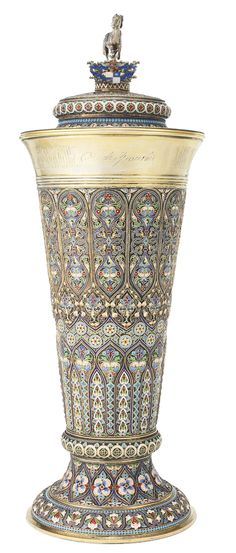 A monumental Russian gilded silver and cloisonné and shaded enamel covered trophy cup, Khlebnikov, Moscow, circa 1895 tapering cylindrical, the lobed body decorated with brightly colored stylized foliate ornament against a stippled gilt ground, the upper rim with a dedicatory inscription, the slip-on lid with conforming ornament and surmounted by the cast and chased figure of a galloping horse with one front hoof resting on an unidentified Russian noble coat-of-arms en plein. $50,000.00