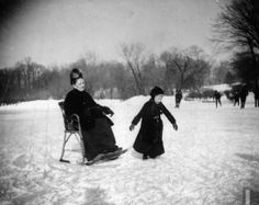 Wallace G. Levison's mother sitting in a special ice-skating chair as a young boy skates near her on the Prospect Park Skating Lake, Brooklyn, New York, February 13, 1888
