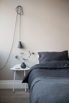 Soft, dusty pink walls with dark grey linen bedding, a beautiful and simple bedroom