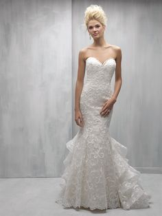 MJ252-Madison James  Bold patterned lace appliques pair perfectly with this chic gown's ruffled train.  Colors:Ivory, Ivory/Champagne Fabrics:Lace