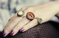 Gorgeous DIY Button Rings... The tutorial for these rings are great and super easy to follow. I love the fact that you can make a bunch of them with mixed and matched buttons.  Do you take the buttons off from old ruined clothes before you throw them away? My mom always did!  #diy #crafts
