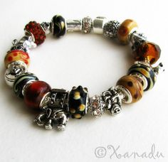 Going On Safari European Style Charm Bracelet - Black, Brown, Taupe Lampwork Glass And Silver Beads on Silver Snake Chain with Snap Clasp. $34.95, via Etsy.