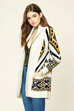 A knit cardigan featuring an allover tribal print, a longline silhouette, two front pockets, long raglan sleeves, a shawl collar, and a ribbed trim.