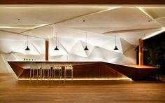meuble bar design en bois massif avec éclairage indirect intégré et un mur facetté blanc comme accent