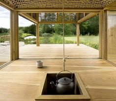 Visitors to this timber tea house sit beneath a woven rope dome with a gilded skylight and a hanging teapot in the middle.