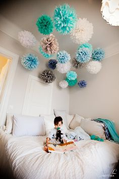 Pom Poms. I am going to literally make these. out of tissue paper and do this in blue, yellow and purple and dark green.