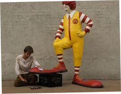 """Banksy a New York.  La tirannia del fast-food (16 ottobre) Un grande Ronald Mc Donald - il pagliaccio in fibra di vetro simbolo della catena di ristoranti - si fa lucidare le scarpe da un ragazzo in carne ed ossa. L'installazione intitolata Shoe Shine è una """"denuncia del duro lavoro necessario a mantenere l'immagine lucida e immacolata (come un paio di scarpe) dell'azienda"""". L'opera sarà riproposta per una settimana ogni giorno davanti a un Mc Donald's diverso della città."""