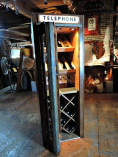 """The team converted the antique phone booth into some """"spirited"""" storage with both crisscross and display sections for wine bottles."""