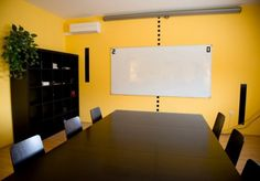 Simple wall shades with a tinge of greenery to match the yellow of the wall and the brown of the wood for the conference room.