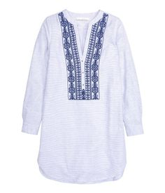 V-neck tunic in woven cotton fabric with long sleeves with button at cuffs. Rounded hem, slightly longer at back.