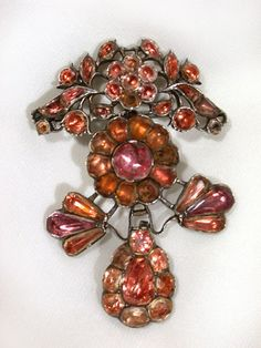 "Pendant Brooch: ca. 1760-1770, Portuguese or Spanish, floral spray on pendeloque set with foiled topaz skips (pink to practically orange) onto a sculptured silver back. ""Pretension, ostentatious, and spectacle were the words of the day for the late 17th and 18th centuries. The aristocratic and wealthy Spaniards and Portuguese continued with this tradition longer than did those caught up by the tides of revolution in Europe and England..."""