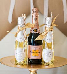 Mini champagne bottle favors with striped straws Ashley Lindzon