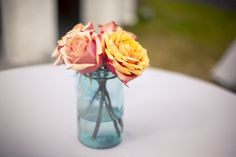Such a #gorgeous #color #combination! Love the #peach #pink, #yellow #orange #roses with the #blue #glassjar. #Simple #beauty can be so #striking + #personalityfilled! ::Sarah + Zach's bright + cheery wedding at the Savannah Railroad Roundhouse and Museum in Georgia:: #weddingflowers #centerpieceideas #weddingdecor #eventdesign #cutecolors #colorscheme #weddingideas #weddingphotography #flowers #floraldesign