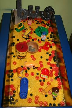 Wheels on the Bus Sensory Bin- yellow rice, red & black wagon wheel pasta, buses, coins and coin can, school toys