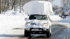 A vehicle, with a large chunk of snow on it's top, drives along Route 20 after digging out after a massive snow fall in Lancaster, N.Y., Nov. 19, 2014.