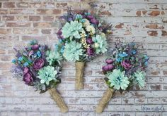 This wildflower bouquet is full of purple, teal, turquoise, and lavender wildflowers and blossoms. Absolutely gorgeous! The center bouquet is a bridal bouquet, and the bouquets on the sides are bridesmaid bouquets. Perfect silk flower wedding set! Shown wrapped in burlap and twine, this rustic wedding bouquet can be purchased in a bridal size (center bouquet) or a bridesmaid bouquet size (outer bouquets). The bridal bouquet pictured is our medium size, and is about 8-10 wide and about 12-14…