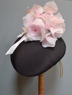 Black silk crepe.  Trimmed with hand-made organza hydrangea.