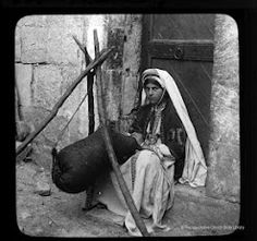 """churning butter from """"Images of a tour in Palestine 100 years ago"""" http://ireland.anglican.org/about/144  (from the dress and headpiece, I would guess she was from Ramallah)"""