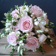 Wedding bouquet of sweet avalanche roses, lisianthus, snowberry, hydrangea, freesia