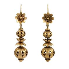 1930s Antique Style Gold Earrings. A pair of gold earrings in the antique style comprised of florette tops and graduated openwork bead pendants, in 18k.