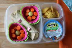 Spring  Lunchbox: Peanut Butter and Banana Wrap, carrots and grapes in muffin cups, a Mott's Medley Cherry Berry cup and some crunchy corn chips.
