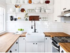 Beautiful IKEA apartment kitchen! Chef's block counter, farm sink, simple shelves, subway tile