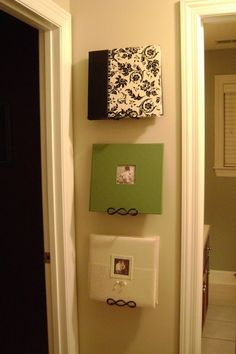 use plate hangers to display photo albums. This is so much more awesome than having them rot on a shelf! Genious :]