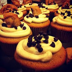 Cookie dough cupcakes filled with cookie dough and topped with cookie dough frosting mini chocolate chips and a chocolate chip cookie