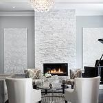 living rooms - gray blue canvas flanking fireplace stone granite white stone club chair circular glass woodgrain contemporary grand piano silver glitter pendant chandelier crystal