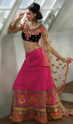 Flaunt your elegance of style, taste and manner dressed in pink color embroidered velvet, net and chiffon choli skirt. The enticing lace, resham and stones work a considerable element of this attire. #indianlooklehengacholi #longlehengacholis #indianwearlehengas