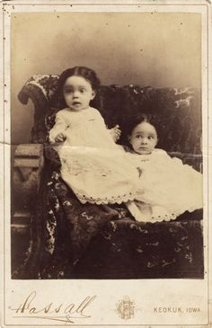 Two cute little girls in white dresses trimmed with lace posing for a studio portrait on a bench covered with a kilim rug, c. 1885. #Victorian #vintage #children #portraits