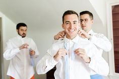 Have the groomsmen lend a helping hand with fastening the groom's tie, putting on their jacket, or buttoning up their cufflinks.