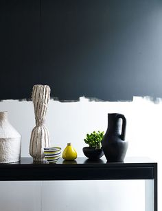 A two-tone wall provides a statement monochrome backdrop for a collection of sculptural vessels in contrasting materials. Blurring the line between the black and white paint adds a soft edge to the display. Styling Claudia Bryant, Photograph Emma Lee, May 2015.  http://www.hglivingbeautifully.com/wp-content/uploads/2015/04/20150128_HomesGardens_Shot6_013.jpg