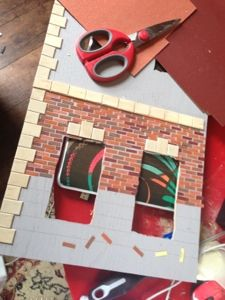 Using various colours of sandpaper as bricks is genius! (maybe use for a fireplace instead of exterior.)