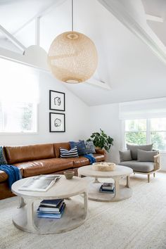 Round white oak coffee tables in this stunning East Hampton Post-Modern living room designed by Chango & Co.