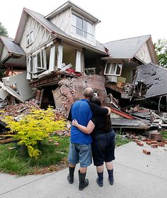 In this Feb. 23, 2011 file photo Murray, left, and Kelly James look at their destroyed house in central Christchurch, New Zealand, a day after a deadly earthquake.