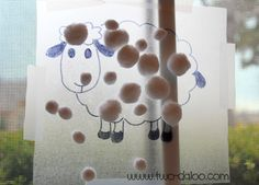 """twodaloo: Contact paper, tape, white pompoms, and a marker. I printed a sheep coloring page from the web (do a search for """"sheep template"""" or """"sheep printable""""), traced it onto the Contact paper with a permanent marker, and taped it sticky-side-out onto a window"""