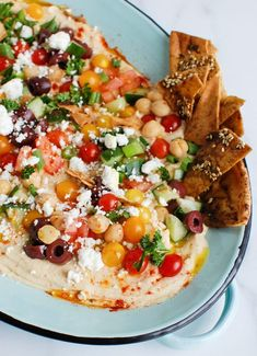 Your guests will love this Hummus Platter at your next outdoor gathering this summer. Creamy hummus is topped with your favorite Mediterranean ingredients like olives, feta cheese, chopped tomatoes and cucumbers, fresh herbs and served with crispy pita chips and fresh vegetables. Add this colorful spread to your table and impress your family and friends! // acedarspoon.com #hummus #appetizer #Mediterraneandiet