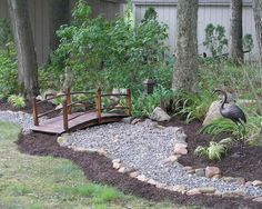 I love the idea of a rock creek bed winding along the back edge of the garden. The footbridge lends a Zen element to the design.
