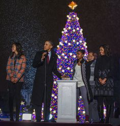 President Barack Obama and daughters Malia and Sasha, mother-in-law Marian Robinson and First Lady Michelle Obama look on from the stage during the 91st national Christmas tree lighting ceremony at the White House December 6, 2013.