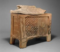 Terracotta larnax (chest-shaped coffin),  Late Minoan IIIB,  mid-13th century B.C., Minoan | The larnax was the standard type of coffin in Crete from the early fourteenth century to the twelfth century B.C. The structure with recessed panels on each side suggests a wooden prototype, and recent scholarship has identified Egyptian chests as the probable models.