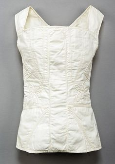 set of young women's trapunto quilted stays, 1820s, of white cotton, with central busk panel, decorative shamrock motifs to the waist, no boning - the structure from the trapunto ribbing