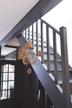 <p>Sobre, simplement peint en gris, l'escalier en bois qui mène aux chambres rappelle la poutre du plafond teinte dans les mêmes tons et fais échos au lustre en perles de bois ...