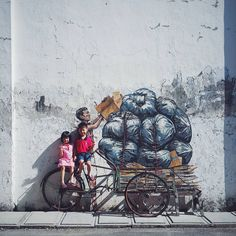 Interacting with the urban architecture of international cities he visits, street artist Ernest Zacharevic (previously here and here) playfully intervenes with structures of both large and small scale. These site-specific works often feature children— either climbing buildings or playing make-be