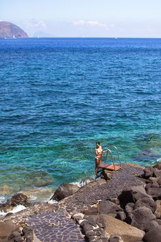 Swimming in the turquoise sea by the rocky cliffs in Vulcano.                                             www.songofstyle.com